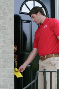 Pest Control Technician leaves a door hanger
